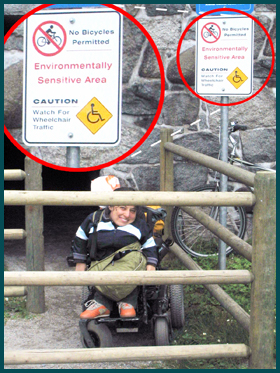 "A student in wheelchair stands next to a sign that reads ""Caution: watch for wheelchair traffic."""